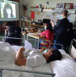 a sala com alunos sentados e um deitado na cama assistem à videoconferência.