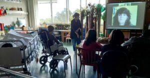 Uma perspetiva geral da sala do espaço escola com camas e cadeiras de rodas. Os alunos e a professora assistem à videoconferência.
