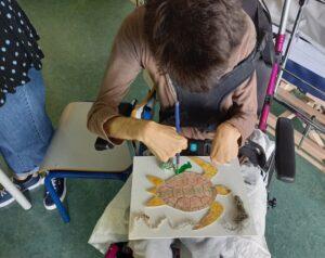 Um aluno pinta o seu quadro sobre a tartaruga marinha.
