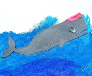 Trabalho final: o cachalote em relevo feito em cartolina e colado sobre um fundo azul e branco e dois exemplares de lixo marinho - um bocado de balão e a tampa de uma lata de bebida a fazer de óculos.