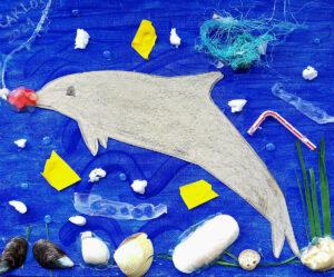 Trabalho final: o golfinho em relevo feito em cartolina sobre um fundo pintado de azul e rodeado de lixo marinho - bocados de balões, fios de pesca, esferovite, palhinha e outros tipos de plástico.