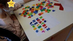 Criança a fazer nomes com letras magnéticas