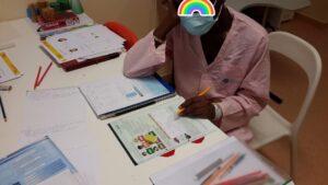 Criança a fazer trabalhos no manual escolar