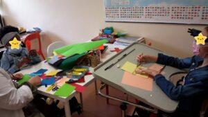 Criança a realizar prenda com recortes de papel