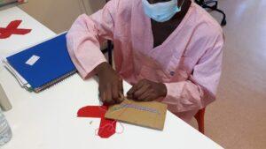 Criança a realizar prenda cosendo em cartão