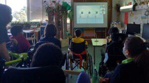 Os alunos olham com atenção para a instalação de Antoni Muntadas.