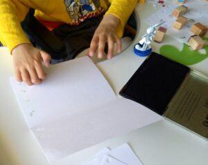 As mãos de um aluno a construir o seu postal com carimbos e furadores.
