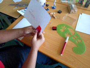 As mãos de um aluno a construir o seu postal.