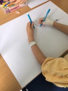 Criança com canetas de feltro a desenhar com as duas mãos em simultâneo