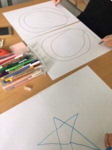 Crianças desenham simetrias em duas folhas com as duas mãos em simultâneo