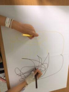 Criança desenha simetrias com duas canetas de cor diferente em duas folhas com as duas mãos em simultâneo