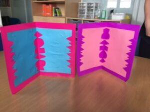 Simetrias (folhas coloridas sobre cartões de cor diferente) com técnica de recorte de folha dobrada pelo centro