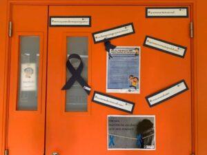Porta da escola com laçao e folhas A4 com explicações sobre o Mês da prevenção dos maus tratos na infância