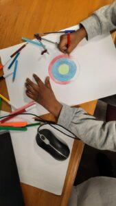 Criança a colorir círculos concêntricos