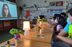 Os alunos escutam, à luz de candeeiros e com frascos com flores em cima das mesas, a Mariana que lhes fala de Lourdes Castro.