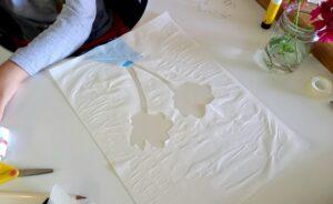 O trabalho de um aluno com recortes em papel vegetal das sombras projetadas pelas glicínias.
