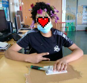 Um aluno com o cabelo enfeitado com flores acaba o seu trabalho de Hapa Zome.