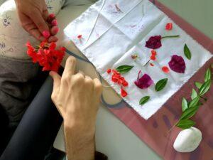 Um pano de algodão branco com flores dispostas sobre ele prontas para serem estampadas com a ajuda de um seixo.