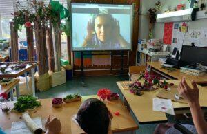A Joana canta para os alunos uma canção sobre flores e os alunos acompanham com gestos.