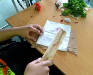 Um aluno faz a estampagem do seu tecido com o auxílio de um pau de madeira.
