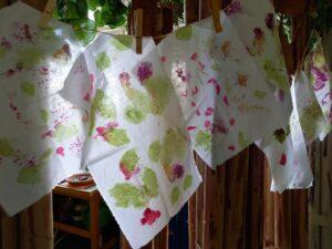 Os tecidos a secar já concluídos, pendurados num fio e presos por molas de madeira, mostram padrões coloridos e simétricos.