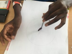 Criança a desenhar círculos concêntricos com um compasso