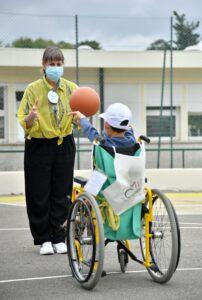 A professora Sónia Bártolo a jogar à bola com um aluno em cadeira de rodas num pátio exterior do Centro de Medicina de Reabilitação de Alcoitão.