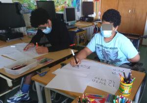 Dois alunos experimentam desenhar e escrever de formas diferentes.