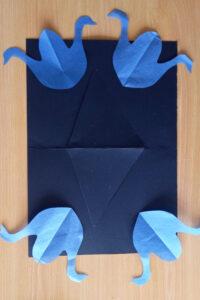 Um trabalho realizado, segundo a técnica de José Escada, com recortes de papel e cartolina: 4 cisnes azuis em cima de uma cartolina preta.