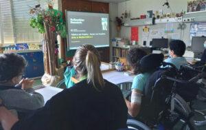 A sala cheia de alunos que observam a videoconferência através do quadro interativo.
