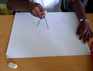 Uma aluna traça uma circunferência com o compasso.