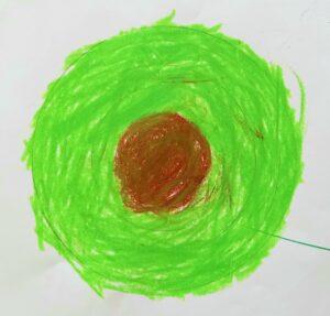 Trabalho de um aluno que representa um círculo concêntrico pintado a lápis de cera.