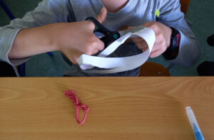 Um aluno recorta a tira de Moebius.