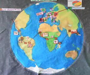 O planeta Terra desenhado e pintado num papel colado na parede, com os países produtores e transformadores assinalados.